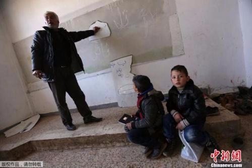 在位于阿勒颇北部的这所学校里,老师用破碎的白板讲课,而学生们坐在地上听课。