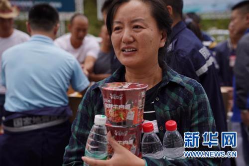 8月9日,在九寨沟黄龙机场,从九寨沟撤出的一名旅客领取方便面和水。新华社记者 才扬 摄