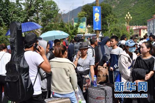 8月10日,在漳扎镇的灾民安置点,民宿及酒店工作人员和部分居民在道路旁等待乘车离开。新华社记者 李鑫 摄