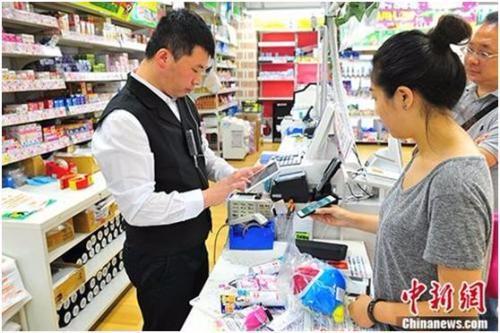"""2017年7月3日,在东京著名繁华街区涩谷的一家商店内,顾客尝试用来自中国企业的""""扫码支付""""付款。 <span target='_blank' href='http://www.chinanews.com/'></div>中新社</span>记者 吕少威 摄"""